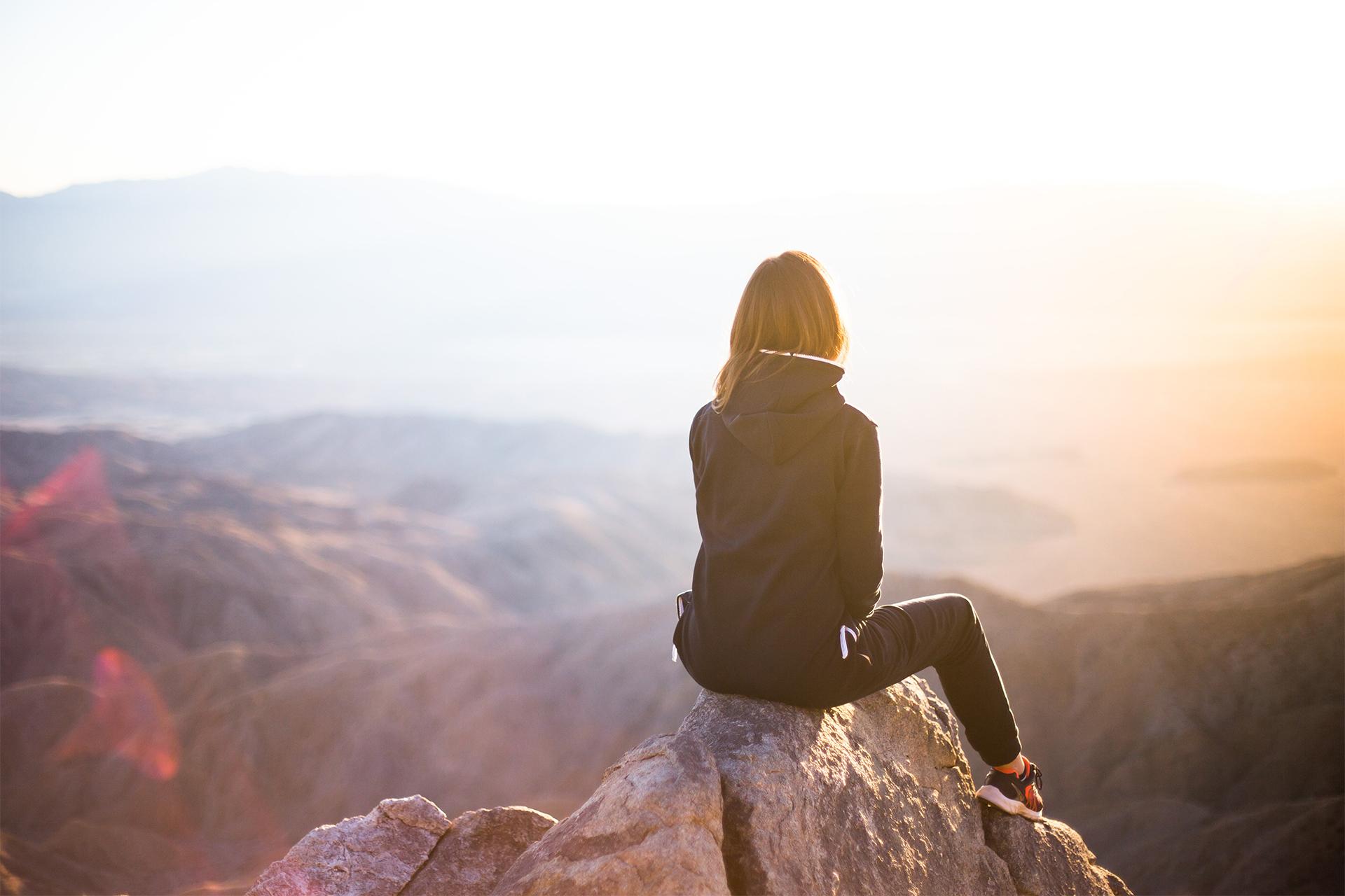 Femme adultes assise sur un rocher à la montagne